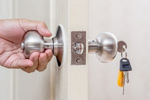 Hand holding door knob with keys